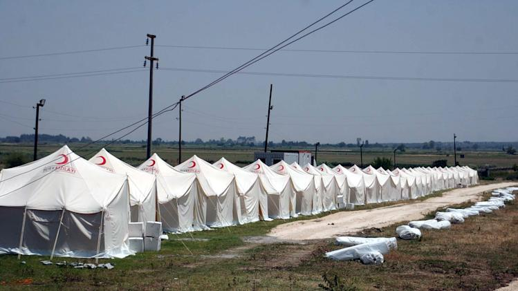 Turkish Red Cresdent workers prepare a new tent city for Syrian refugees in the town of Altinozu, close to the border with Syria, in Hatay province, Turkey, Friday, June 10, 2011. Turkey said Wednesday, that it would open the border to Syrians fleeing violence.(AP Photo/Burhan Ozbilici)