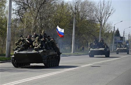 Armed men drive an airborne combat vehicle with a Russian flag seen on the top, outside Kramatorsk