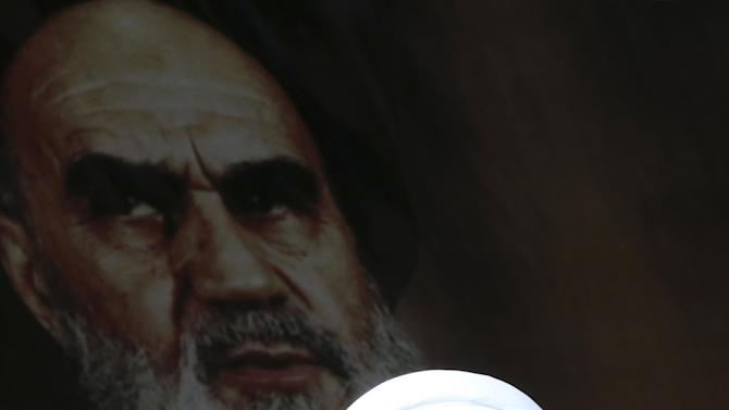 Iranian President Hassan Rouhani delivers his speech under a portrait of the late revolutionary founder Ayatollah Ruhollah Khomeini during a rally to commemorate the anniversary of the 1979 Islamic revolution, at the Azadi (Freedom) Sq. in Tehran, Iran, Thursday, Friday, Feb. 11, 2016. The nationwide rallies commemorate Feb. 11, 1979, when followers of Ayatollah Khomeini ousted U.S.-backed Shah Mohammad Reza Pahlavi. (AP Photo/Vahid Salemi)