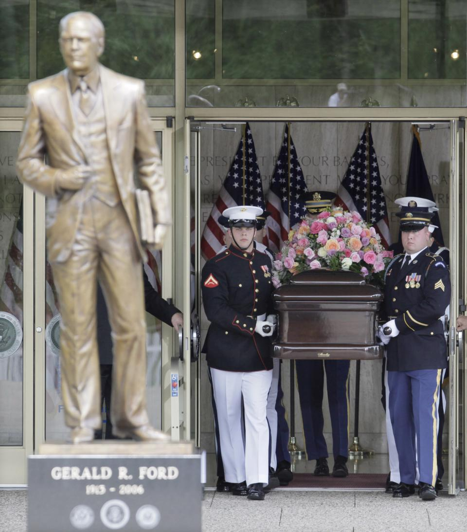 A military honor guard carries the casket bearing the body of former first lady Betty Ford toward a statue of the former President at the Gerald R. Ford Presidential Museum in Grand Rapids, Mich., Thursday, July 14, 2011, prior to funeral services at Grace Episcopal Church. (AP Photo/M. Spencer Green)