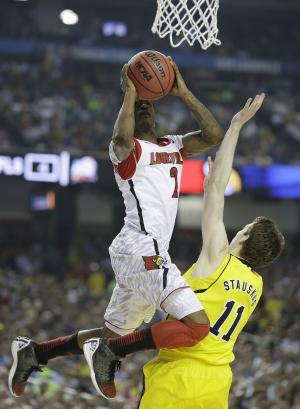 Louisville guard Russ Smith (2) shoots over Michigan guard Nik Stauskas (11) during the first half of the NCAA Final Four tournament college basketball championship game Monday, April 8, 2013, in Atlanta. (AP Photo/Charlie Neibergall)