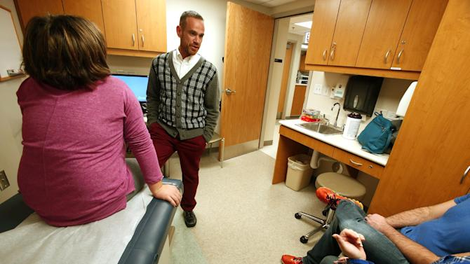 In this photo taken on Tuesday, Nov. 17, 2015, Dr. Robert Garofalo greets a young patient, in Chicago. Garofalo is director of the adolescent medicine division at Lurie Children's Hospital of Chicago, where he is also director of the Center for Gender, Sexuality and HIV Prevention. This child was at the clinic for treatment related to gender. Garofalo had built his medical and research career on helping young AIDS patients. Then in 2010 he learned that he, too, was HIV-positive. (AP Photo/Martha Irvine)