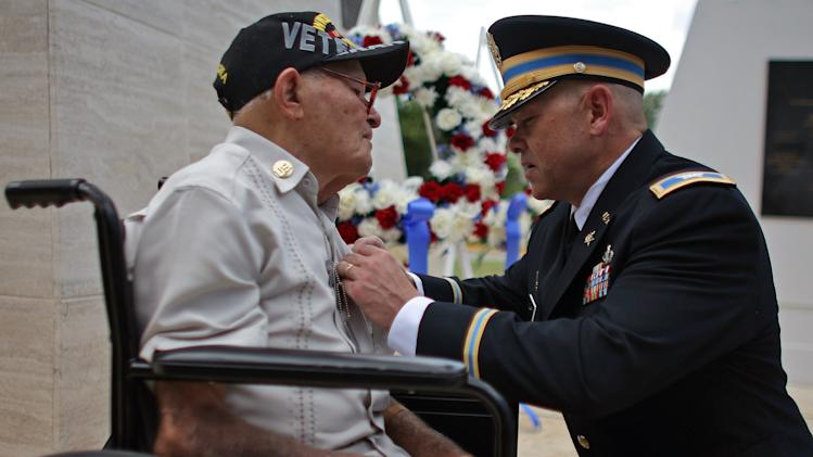 US Army Col. David J. Clark, right, director of the Department of Defense's 60th Anniversary Korean War Commemoration Committee, presents a a Bronze Star to Korean War veteran Luis Ramos, 90, during a ceremony attended by more than a dozen surviving members of the famed 65th Infantry Regiment, in San Juan, Puerto Rico, Friday, Sept. 7, 2012. Ramos, who served with the mostly Puerto Rican unit that fought in some of the bloodiest battles of the war, received belated appreciation from the U.S. military, Friday. (AP Photo/Ricardo Arduengo)