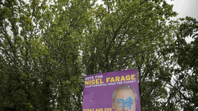 A defaced election poster featuring Nigel Farage, leader of the United Kingdom Independence Party, is seen in Clifsend, southern England