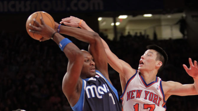 Dallas Mavericks' Lamar Odom, center, tries to pass around New York Knicks' Jeremy Lin, right, and J.R. Smith during the second half of an NBA basketball game in New York, Sunday, Feb. 19, 2012. The Knicks defeated the Mavericks 104-97. (AP Photo/Seth Wenig)