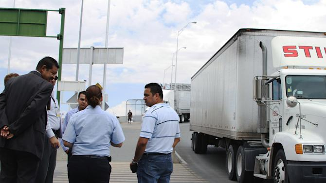 FILE - In this July 5, 2012 file photo, attorney Emilio de La Rosa, left, and forensics expert Mario Gomez, right, talk to customs and court officials at the Las Americas Bridge in Juarez, Mexico while doing a reconstruction of the events that lead to the arrest of trucker Jabin Bogan. Bogan, a Dallas trucker detained for eight months in Mexico on allegations that he tried to smuggle assault rifle ammunition into the country, is expected to return Friday, Nov. 23, 2012, to the United States, his lawyer said. (AP Photo/ Juan Carlos Llorca, File)