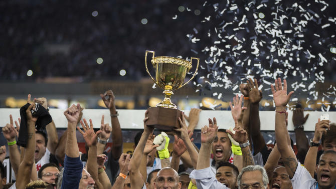 Vasco's Guinazu holds up the Rio de Janeiro state championship trophy as he celebrates with teammates after their team defeated Botafogo 2-1 during the final soccer match at the Maracana stadium in Rio de Janeiro, Brazil, Sunday, May 3, 2015. (AP Photo/Felipe Dana)