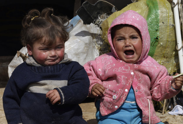 In this Tuesday, Feb. 19, 2013 photo, two Syrian refugee children sit outside their family tent, at Atmeh refugee camp, in the northern Syrian province of Idlib, Syria. This rebel-controlled camp only