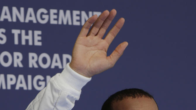 Mercedes driver Lewis Hamilton of Britain waves to the crowd after winning the qualifying session for the Chinese Formula One Grand Prix in Shanghai, China, Saturday, April 13, 2013. (AP Photo/Greg Baker)