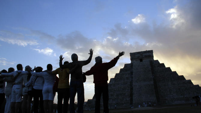 People gesture toward the the Kukulkan temple in Chichen Itza, Mexico, Friday, Dec. 21, 2012. Ceremonial fires burned and conches sounded off as dawn broke over the steps of the main pyramid at the Mayan ruins of Chichen Itza Friday, making what many believe is the conclusion of a vast, 5,125-year cycle in the Mayan calendar. Some have interpreted the prophetic moment as the end of the world. The hundreds gathered in the ancient Mayan city, however, said they believed it marked the birth of a new and better age. (AP Photo/Israel Leal)