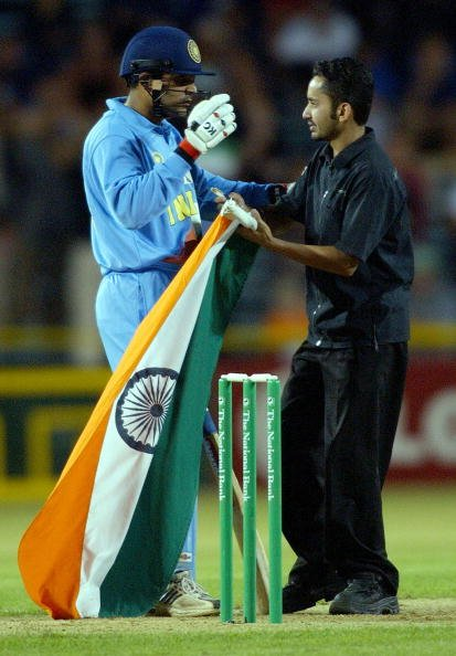 An Indian fan runs onto the field to cogratulate I