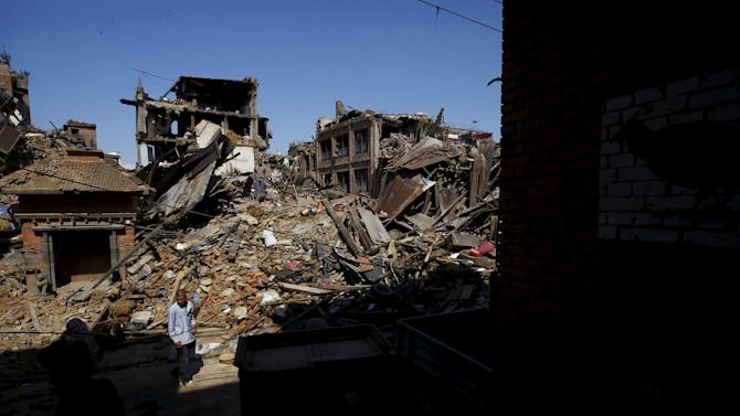 Man walks past collapsed houses following Saturday's earthquake in Bhaktapur, Nepal
