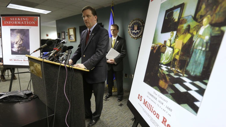 Anthony Amore, chief of security at the Gardner Museum, center, stands next to a poster that shows an image of a Vermeer painting and lists a reward, right, while facing reporters during a news conference at FBI headquarters in Boston, Monday, March 18, 2013. The FBI believes it knows the identities of the thieves who stole art valued at up to $500 million from Boston's Isabella Stewart Gardner Museum more than two decades ago. (AP Photo/Steven Senne)