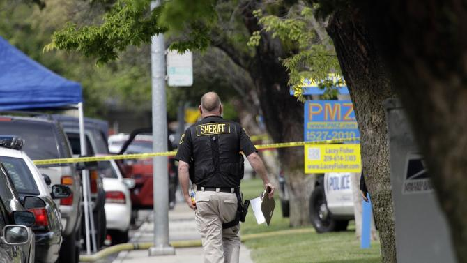 A sheriff's investigator walks in a neighborhood, on Friday, April 13, 2012, where a standoff left a deputy dead a day earlier, in Modesto, Calif.  The standoff began Thursday morning after gunfire broke out as two Stanislaus County deputies went to the Whispering Woods development to serve an eviction notice. A deputy and civilian were killed, and the suspect immediately barricaded himself inside an apartment. Authorities prepared Friday to enter the fire-gutted, California apartment where they expected to find the suspect in the shooting deaths. (AP Photo/Marcio Jose Sanchez)