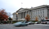 Vehicles drive by the US Treasury Building in Washington on November 15, 2011. Treasury Secretary Timothy Geithner has warned the nation will reach its $16.39 trillion debt limit on December 31