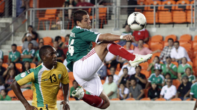 Javier Hernandez of Mexico takes a shot at the goal past Charles Pollard of Guyana during their 2014 World Cup qualifying soccer match.