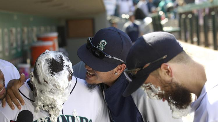 Seattle Mariners' Felix Hernandez, center, jokes around with teammates Fernando Rodney, left, and Dustin Ackley, after Rodney was hit with a pie following the Mariners' baseball game against the Baltimore Orioles in Seattle, Saturday, July 26, 2014. The Mariners won 4-3. (AP Photo/Stephen Brashear)