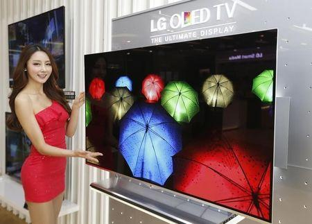 A model poses next to LG Electronics' OLED television in Seoul