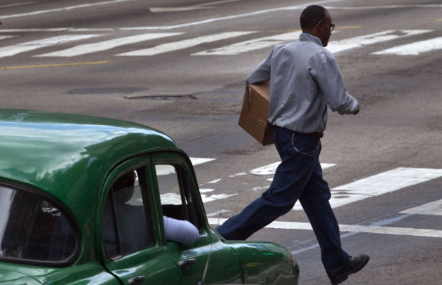 A man runs across a street in front of a slow moving car in Havana, Cuba, Monday, March 4, 2013. Jaywalking is endemic in Havana, where islanders seem to treat the streets like a real-life version of