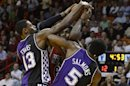 Miami Heat's James is defended by Sacramento Kings' Evans and Salmons during NBA basketball game in Miami