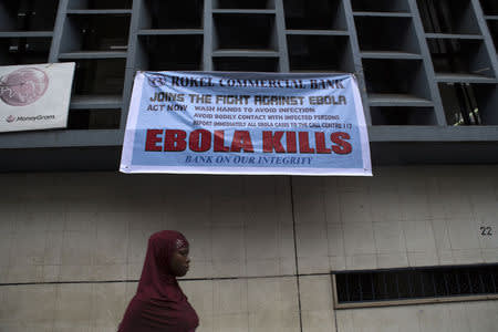 A woman passes a sign posted in an awareness campaign against the spread of Ebola in Freetown