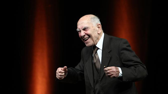 """FILE - This Jan. 19, 2012, file photo shows Stephane Hessel sharing a laugh at the end of a debate on the topic """"France, reasons for hope"""", as part of French presidential candidate Francois Hollande's campaign visit, in Nantes, western France. Stephane Hessel, a concentration camp survivor and member of the French resistance whose 32-page book """"Time for Outrage"""" became a bestseller and an inspiration for the left in Europe and the U.S., has died at 95. (AP Photo/David Vincent, File)"""