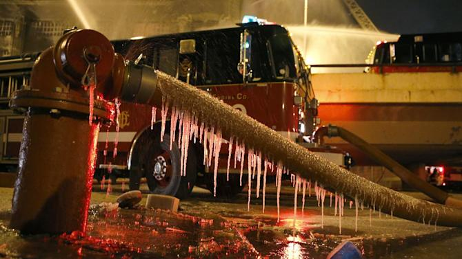 Icicles form on a fire hose from single digit temperatures as Chicago firefighters battle a five-alarm blaze in a warehouse on the city's South Side, Bridgeport neighborhood Wednesday, Jan. 23, 2013, in Chicago. (AP Photo/Charles Rex Arbogast)