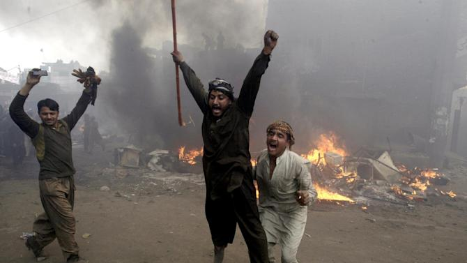 AP10ThingsToSee - Pakistani men, part of an angry mob, react after burning belongings of Christian families in Lahore, Pakistan, Saturday, March 9, 2013. A mob of hundreds of people in the city attacked a Christian neighborhood and set fire to homes after hearing accusations that a Christian man had committed blasphemy against Islam's prophet. (AP Photo/K.M. Chaudary, File)