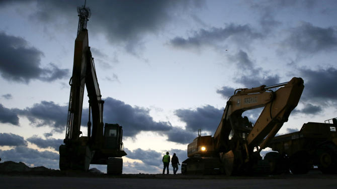 In early morning darkness, workers prepare heavy machinery for the day as rebuilding work continues on the beach area of Seaside Heights and Seaside Park, N.J., Tuesday, Oct. 29, 2013. Tuesday marks the one-year anniversary of Superstorm Sandy. A large Sandy-related fire on the boardwalk in September has slowed progress in the area. (AP Photo/Mel Evans)