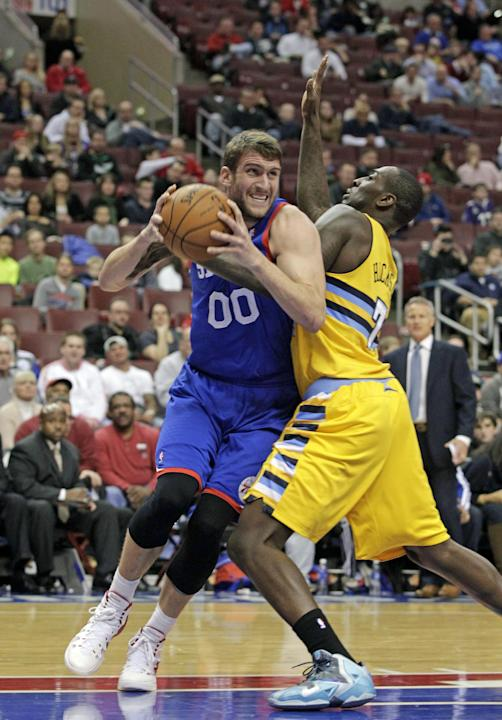 Denver Nuggets'  JJ Hickson (7) defends as Philadelphia 76ers' Spencer Hawes (00) looks to pass in the first half of an NBA basketball game Saturday Dec. 7, 2013, in Philadelphia. The Nuggets
