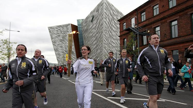 Karen Marshall, the first torch bearer from Northern Ireland, carries the Olympic torch to start the relay from Titanic Museum, background center, in Belfast, Northern Ireland, Sunday, June 3, 2012. (AP Photo/Peter Morrison)