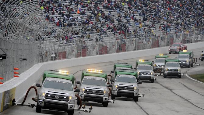 Workers dry the track before the NASCAR Sprint Cup series auto race at Atlanta Motor Speedway, Sunday, March 1, 2015, in Hampton, Ga. (AP Photo/John Amis)