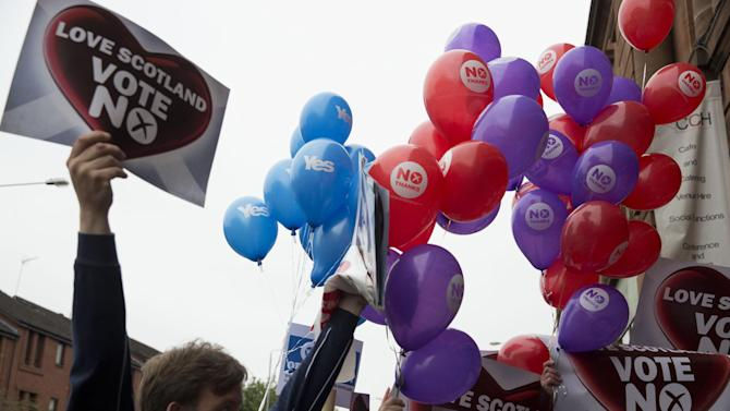 Balloons held by Yes supporters float next to balloons and posters held by No supporters after a No campaign event where a number of speeches were made by different people and politicians in Glasgow, Scotland, Wednesday, Sept. 17, 2014.  Will the ayes have it, or will Scotland say naw thanks?  No one is certain. Excitement and anxiety mounted across the country Wednesday, the final day of campaigning before Thursday's referendum on independence.  With opinion polls suggesting the result is too close to call and turnout expected to reach record levels, supporters of separation feel they are within touching distance of victory — but wonder whether their surge in the polls will be enough.  (AP Photo/Matt Dunham)