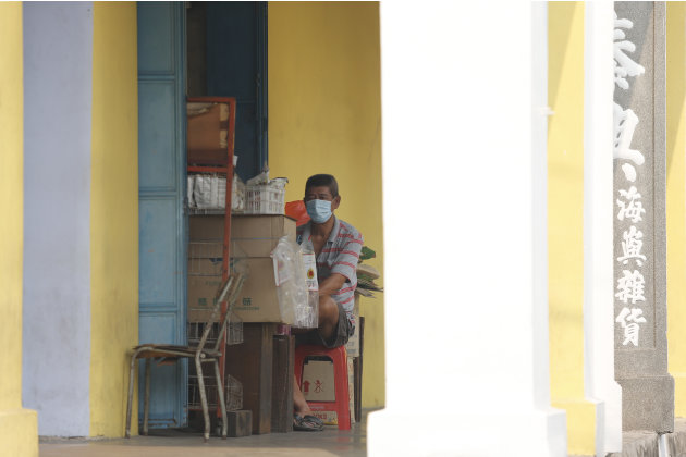 A shopkeeper wears a face mask amid the haze as he waits for customers in Muar