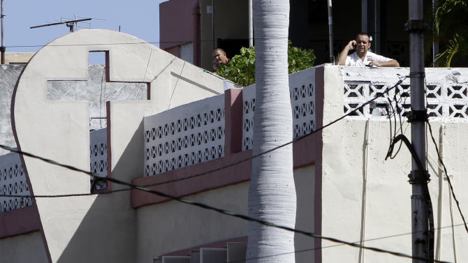 William Herrera, son of the Church's pastor Braulio Herrera, right, speaks on a cellphone during an interview with The Associated Press on the roof of the Assembly of God Pentecostal Church in Havana, Cuba, Tuesday, Sept. 13, 2011. The church's pastor Braulio Herrera along with 60 believers remain in spiritual retreat since last Aug. 21. The police have cordoned off the area around the church to avoid incidents. (AP Photo/Franklin Reyes)