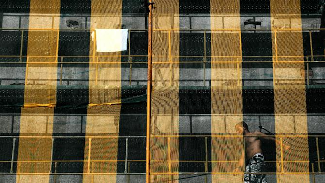 A worker walks on scaffoldings that covers a building under construction in Athens on Thursday, Sept. 6, 2012. Greece's unemployment rate surged to 24.4 percent in June as the number of people out of work in June rose by 34,000 to more than 1.2 million. (AP Photo/Petros Giannakouris)