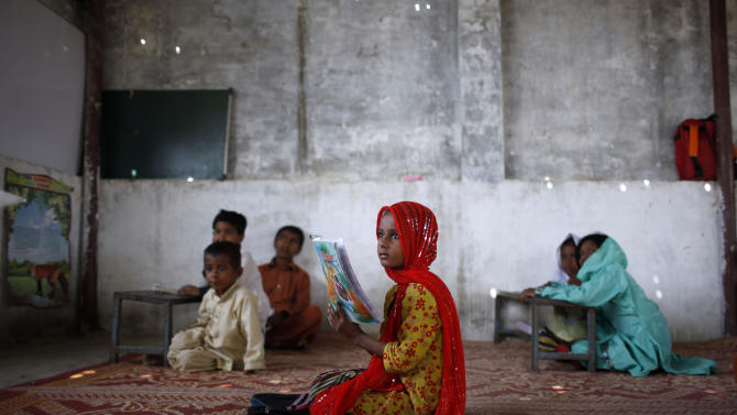 In this Thursday, Oct. 11, 2012 photo, Pakistani schoolgirl Nisha Nadeem, 6, center, attends her class at her school in a slum on the outskirts of Islamabad, Pakistan.  A teenage activist recently shot and critically wounded by the Taliban risked her life to attend school, but the threat from the militant group is just one of many obstacles Pakistani girls face in getting an education. Others include rampant poverty, harassment and the government's failure to prioritize education spending. (AP Photo/Nathalie Bardou)