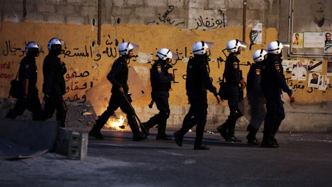 """Riot police look for Bahraini anti-government protesters during clashes after the funeral for a 17-year-old boy in Bani Jamra, Bahrain, on Wednesday, Oct. 23, 2013. Authorities said Ali al-Sabagh was killed when an explosive device he was carrying detonated prematurely as he attempted to stage an attack in the tense Gulf nation. Graffiti on the wall includes, """"steadfast, resistance, unity"""" and a religious verse about fighting injustice. (AP Photo/Hasan Jamali)"""