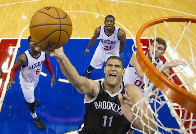 Brooklyn Nets' Brook Lopez goes up for the shot as Philadelphia 76ers' Tony Wroten, left, Thaddeus Young, center, and Spencer Hawes, right, watch during the first quarter of a preseason NBA basketball