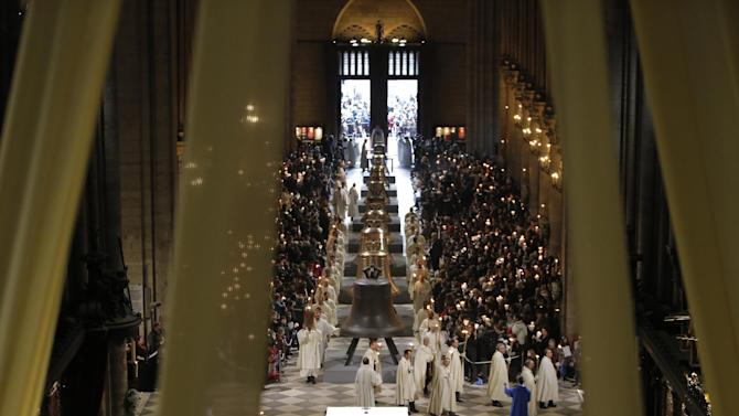 The nine new bronze bells are displayed in Notre Dame cathedral during a ceremony of blessing by Paris Archbishop Andre Vingt-Trois in Paris, Saturday, Feb. 2, 2013. Nine enormous new bronze bells have made their way at Notre Dame Cathedral, helping the medieval edifice to rediscover its historical harmony. (AP Photo/Francois Mori)