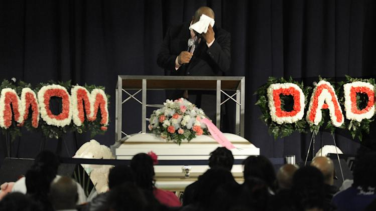 Rev. Corey Brooks wipes his face while speaking during six-month old Jonylah Watkins' funeral at New Beginnings Church in Chicago, Tuesday, March, 19, 2013.  Jonylah's death was the latest to draw national attention to Chicago's struggle with gang violence and murder.  (AP Photo/Paul Beaty)
