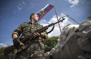 A pro-Russian separatist guards a road checkpoint outside …