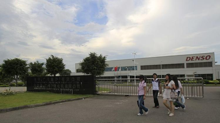 Denso worker walk outside at car parts supplier, Denso (Guangzhou Nansha) Co Ltd in Nansha at the southern Chinese Guangdong province