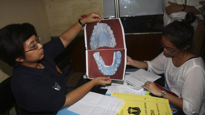 A police forensic officer inspects dental record of a passenger aboard the crashed Sukhoi Superjet-100 for identification purpose at Halim Perdanakusumah Airport in Jakarta, Indonesia, Friday, May 11, 2012. Rescue teams used climbing gear to scale the nearly sheer slopes of a dormant Indonesian volcano, hoping Friday to reach the wreckage of a Russian-made jetliner that crashed with 45 people aboard during a demonstration flight for potential buyers. (AP Photo/Tatan Syuflana)