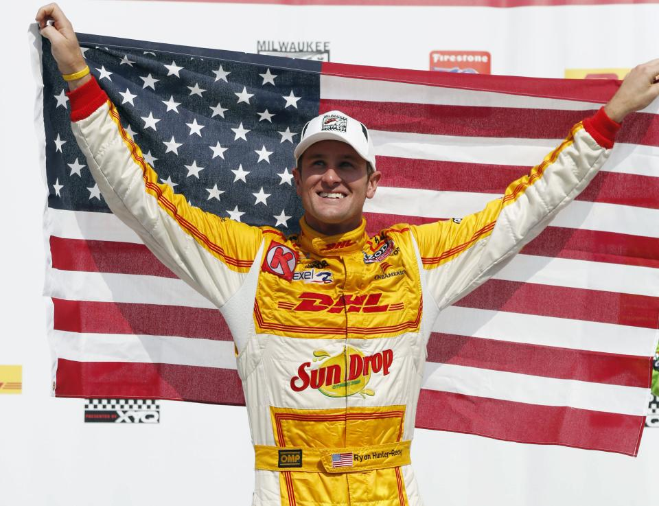 Ryan Hunter-Reay holds up a U.S. flag after winning the IndyCar auto race at the Milwaukee Mile in West Allis, Wis., Saturday, June 16, 2012. (AP Photo/Jeffrey Phelps)