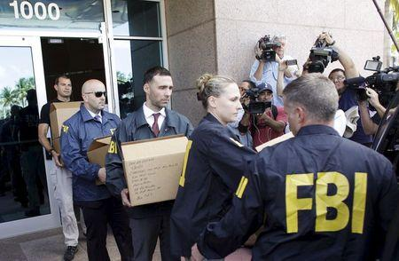 FBI agents bring out boxes after an operation inside the CONCACAF offices in Miami Beach, Florida