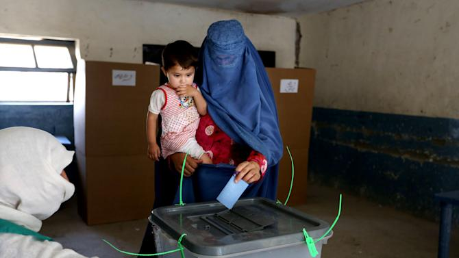 An Afghan woman casts her vote at a polling station in Jalalabad, east of Kabul, Afghanistan, Saturday, June 14, 2014. Despite Taliban threats of violence, many Afghans vow to cast ballots in Saturday's presidential runoff vote with hopes that whoever replaces Hamid Karzai will be able to provide security and stability after international forces wind down their combat mission at the end of this year. (AP Photo/Rahmat Gul)