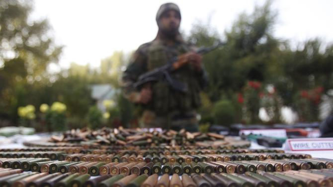 An Indian army soldier stands behind a display of seized arms and ammunition at a garrison in Srinagar