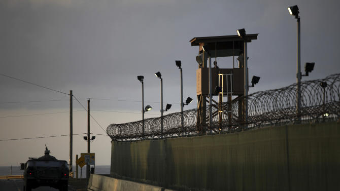 FILE – In this March 30, 2010, file photo reviewed by the U.S. military, a U.S. trooper stands in the turret of a vehicle with a machine gun, left, as a guard looks out from a tower at the detention facility of Guantanamo Bay U.S. Naval Base in Cuba. Guantanamo Bay detainee Musa'ab Omar A Madhwani says in a federal court declaration he feels abandoned by President Barack Obama and the world after more than 10 years at the U.S. prison.(AP Photo/Brennan Linsley, File)