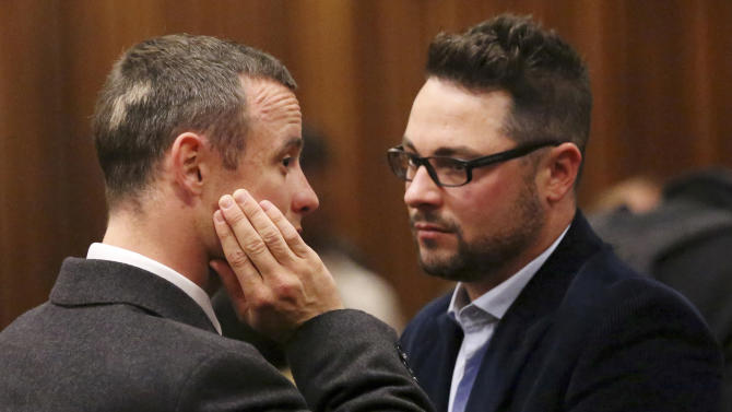 """FILE - In this Tuesday May 20, 2014 file photo brother of murder accused, Oscar Pistorius, left, Carl Pistorius, right, speaks with his brother in court in Pretoria, South Africa. Carl Pistorius has been """"badly hurt"""" in a car accident after a head-on collision on a highway in South Africa, Friday, Aug. 1, 2014. (AP Photo/Siphiwe Sibeko, Pool, File)"""